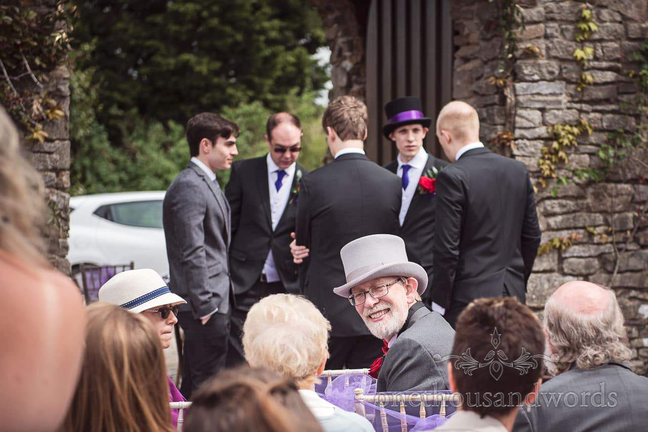 Father of the bride in top hat smiles at groomsmen await arrival of the bride