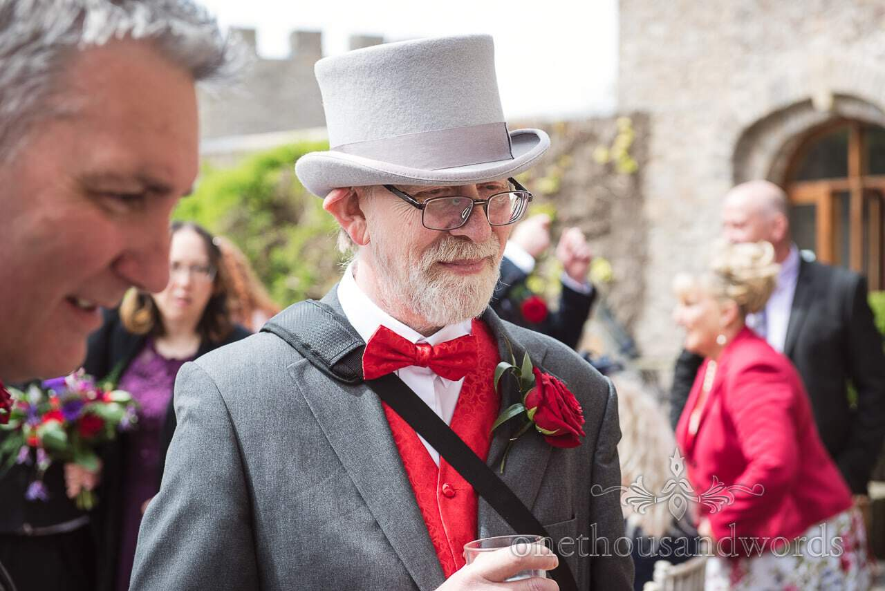 Father of the groom in top hat with red bow tie and red rose at wedding