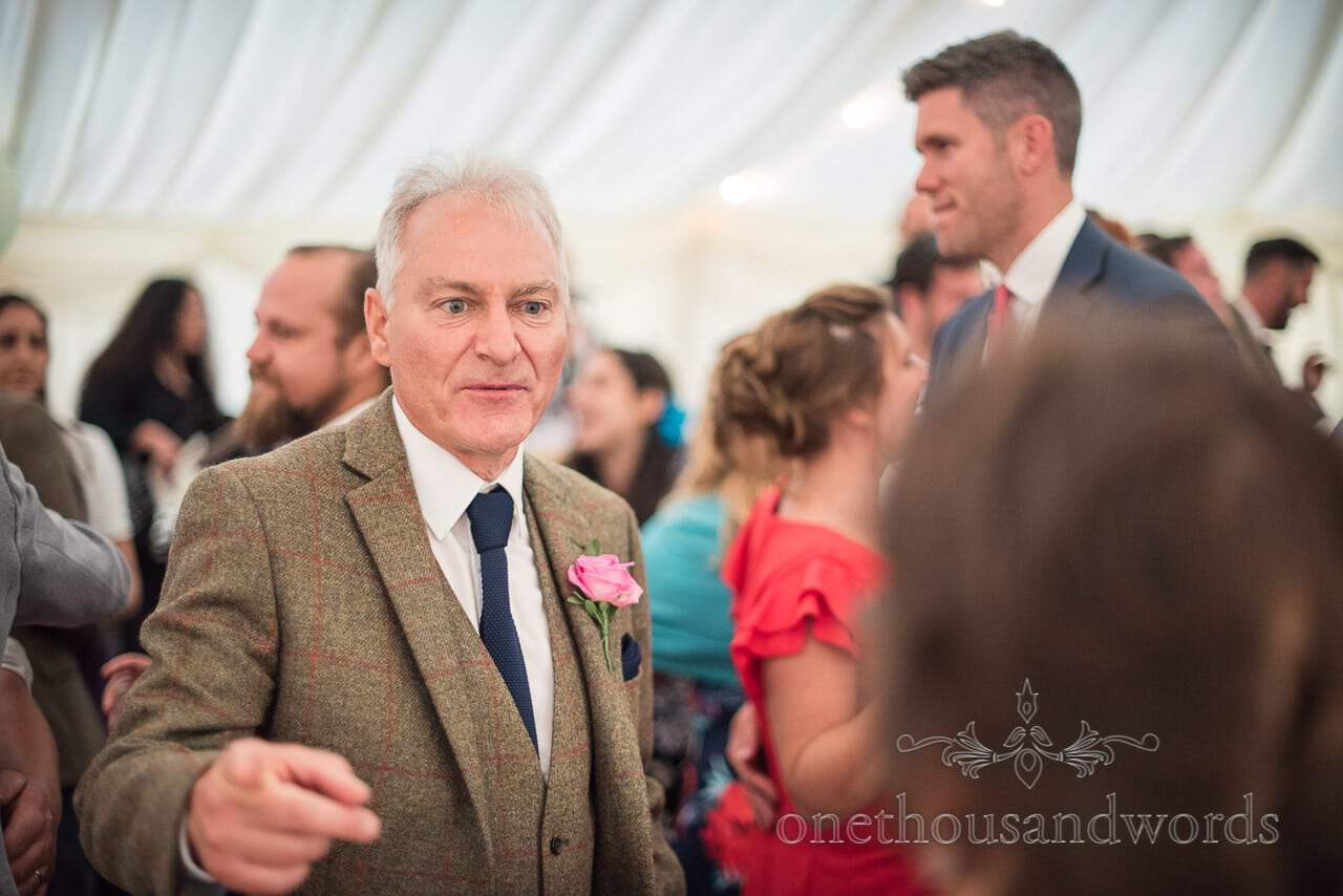 Father of the groom in tweed suit dancing to wedding band in marquee