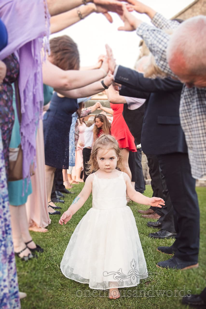 Flower girl emerges from guest guard of honor from Swanage Wedding Photos