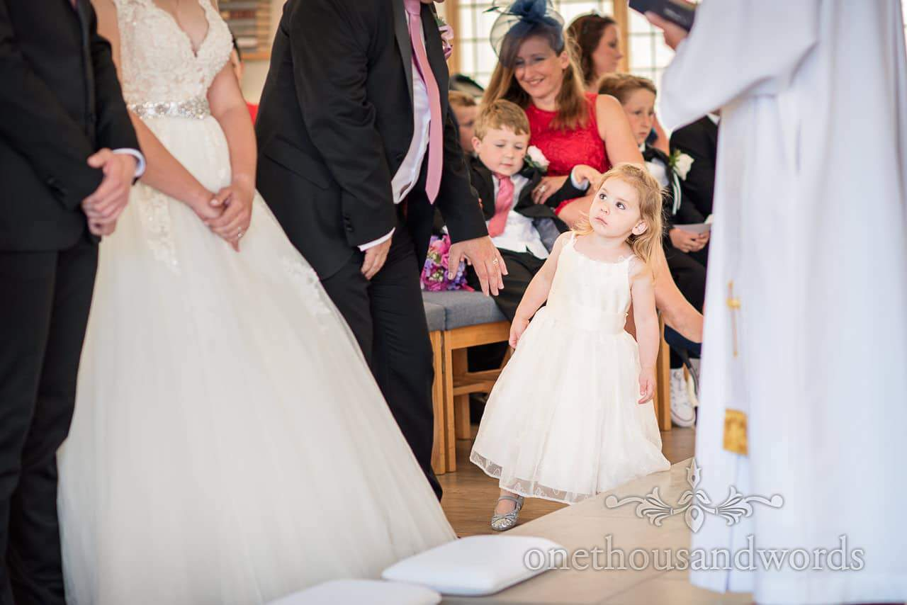 Flower girl looks to see what's going on from Swanage wedding photos