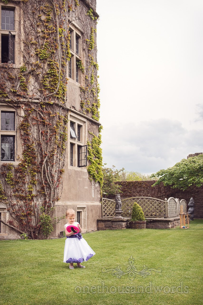 Flower girl plays with wedding lawn games in front of Walton Castle wedding venue