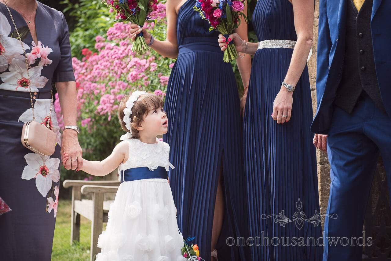 Flower girl waits with bridesmaids outside church from Countryside Wedding Photos