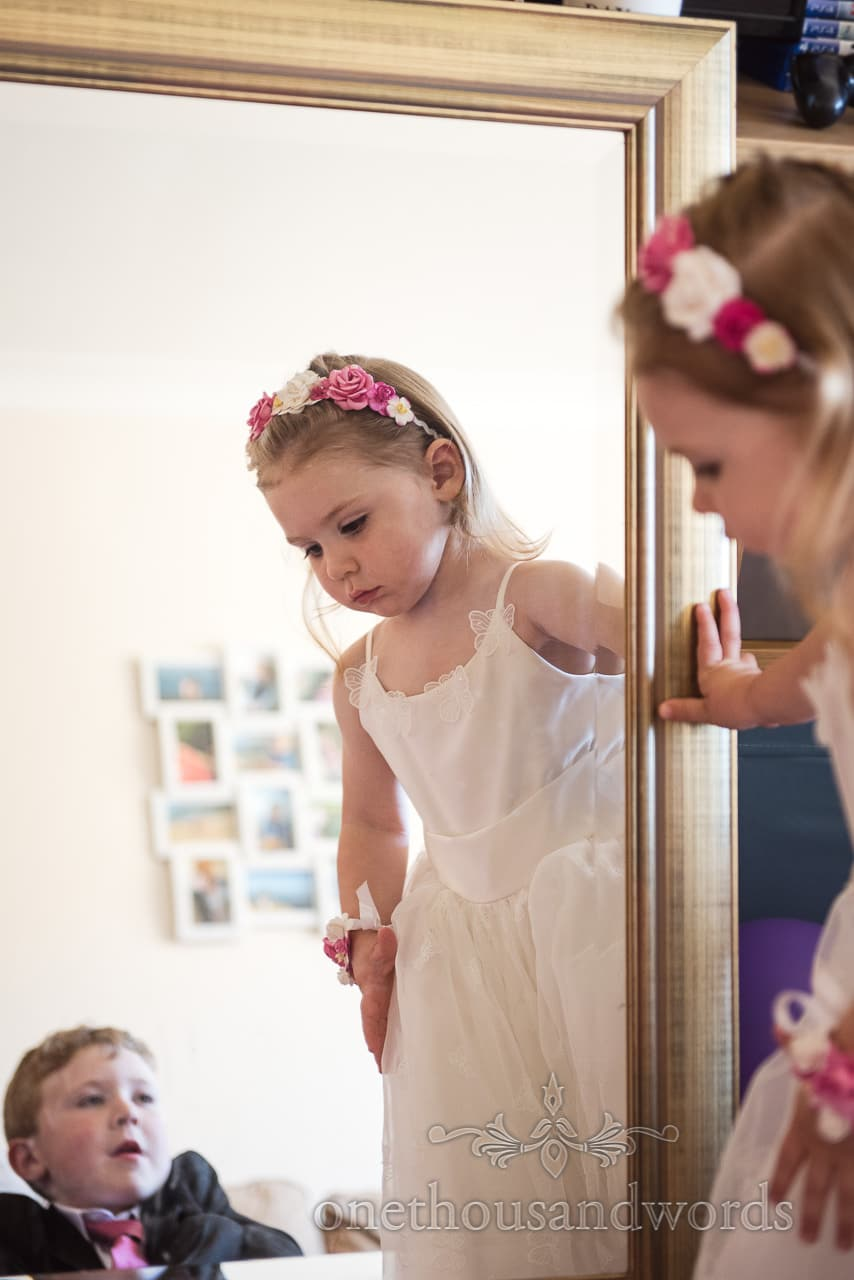 Flower girl with flowers in her hair in mirror from morning of Swanage Wedding Photos