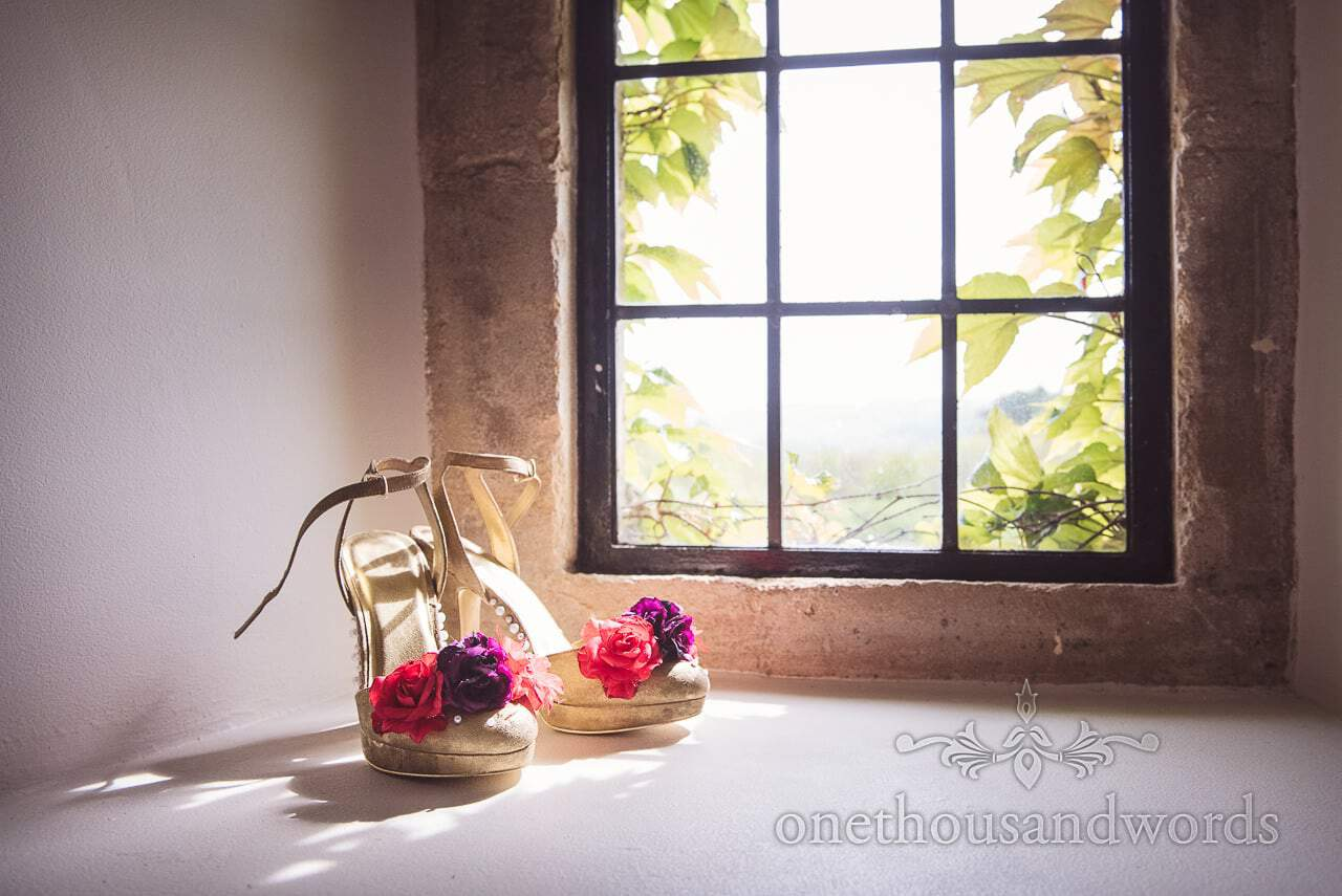 Golden wedding shoes decorated with pearls and red and purple flowers