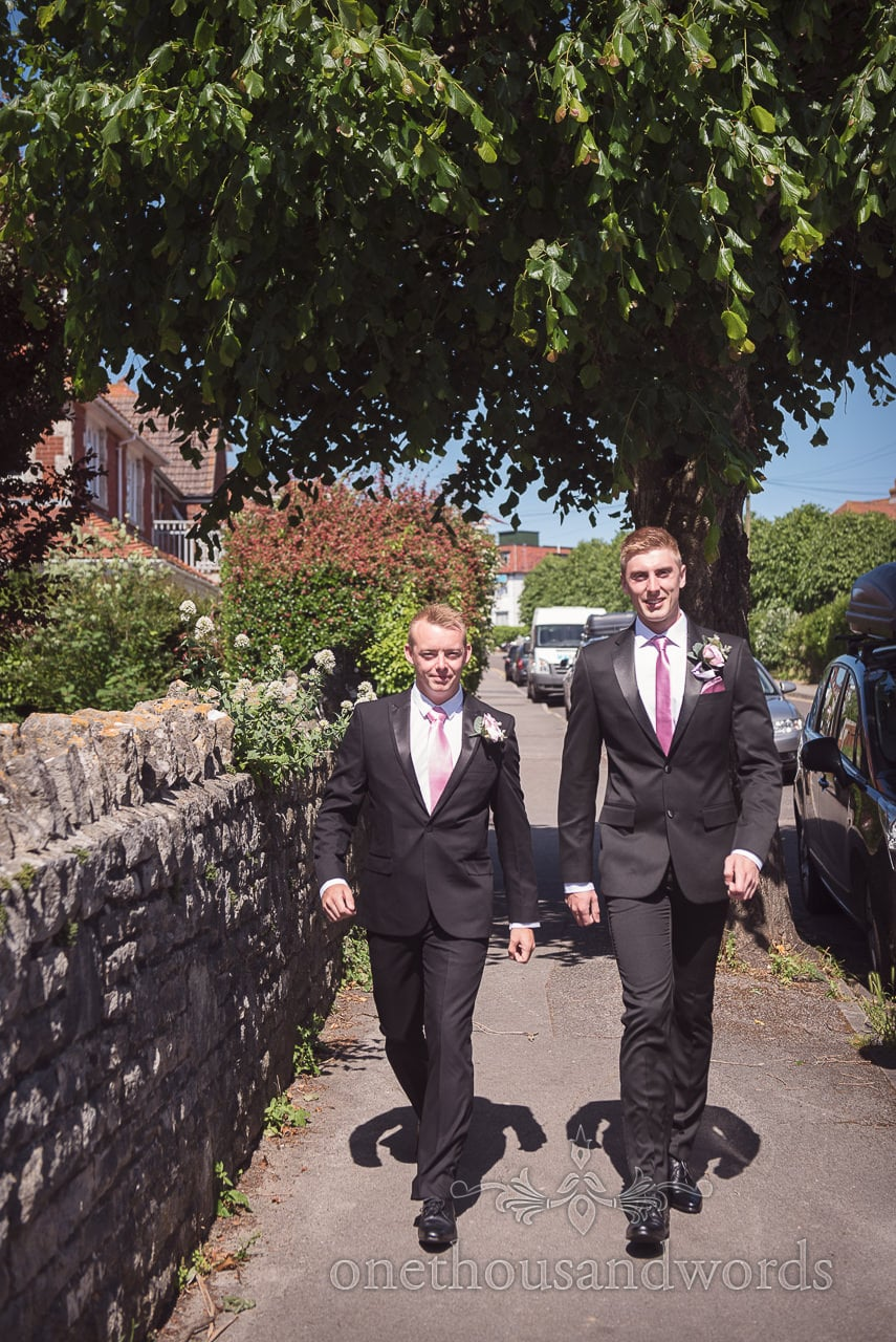 Groom and best man walk to church in the sunshine at Swanage wedding photos