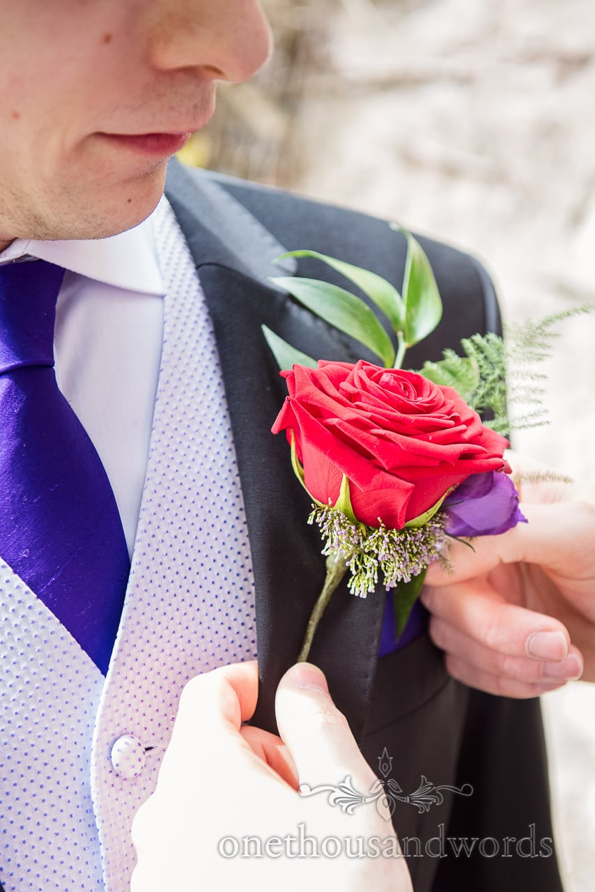 Groom has red rose buttonhole pinned from Chocolate Themed Wedding Photographs