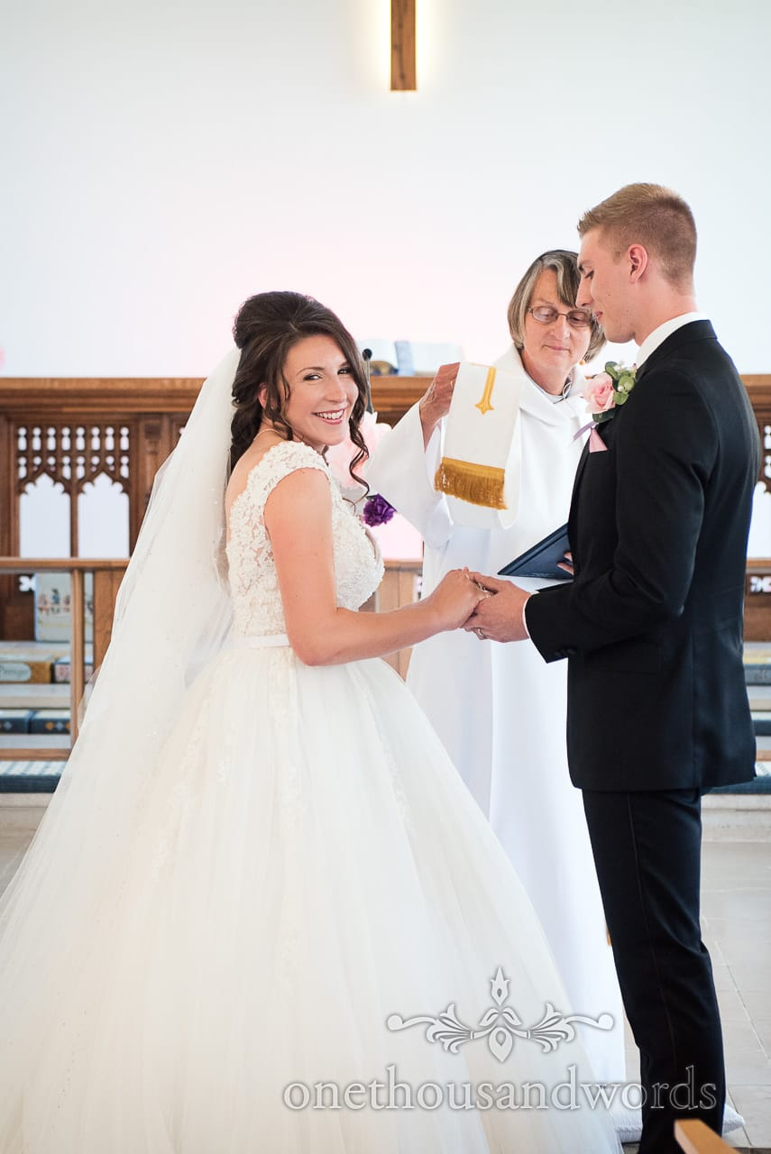 Groom hold brides hand for blessing of the marriage at Swanage wedding