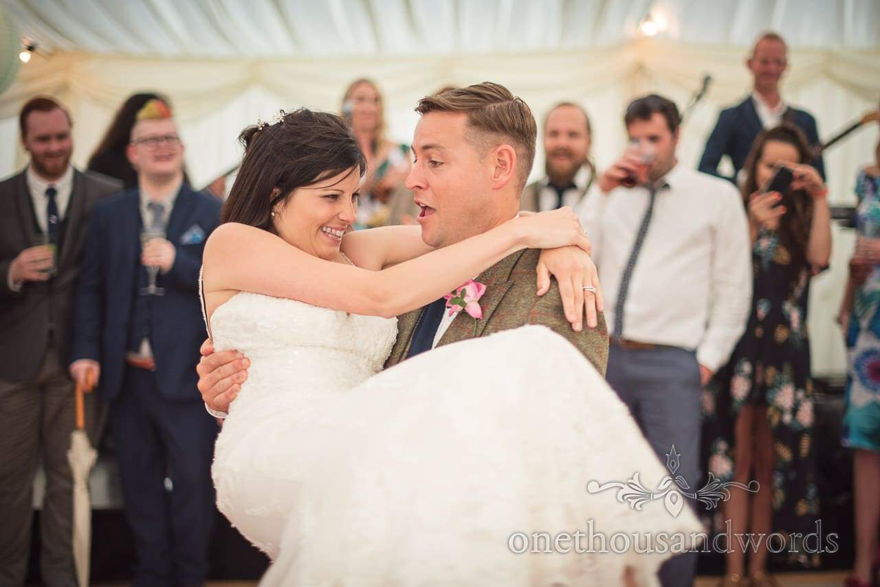 Groom lifts bride as part of choreographed first dance in wedding marquee