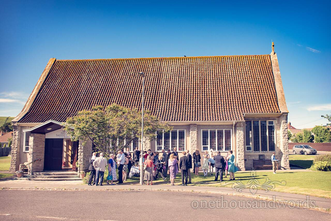 Guests gather outside church for drinks reception from Swanage wedding photos