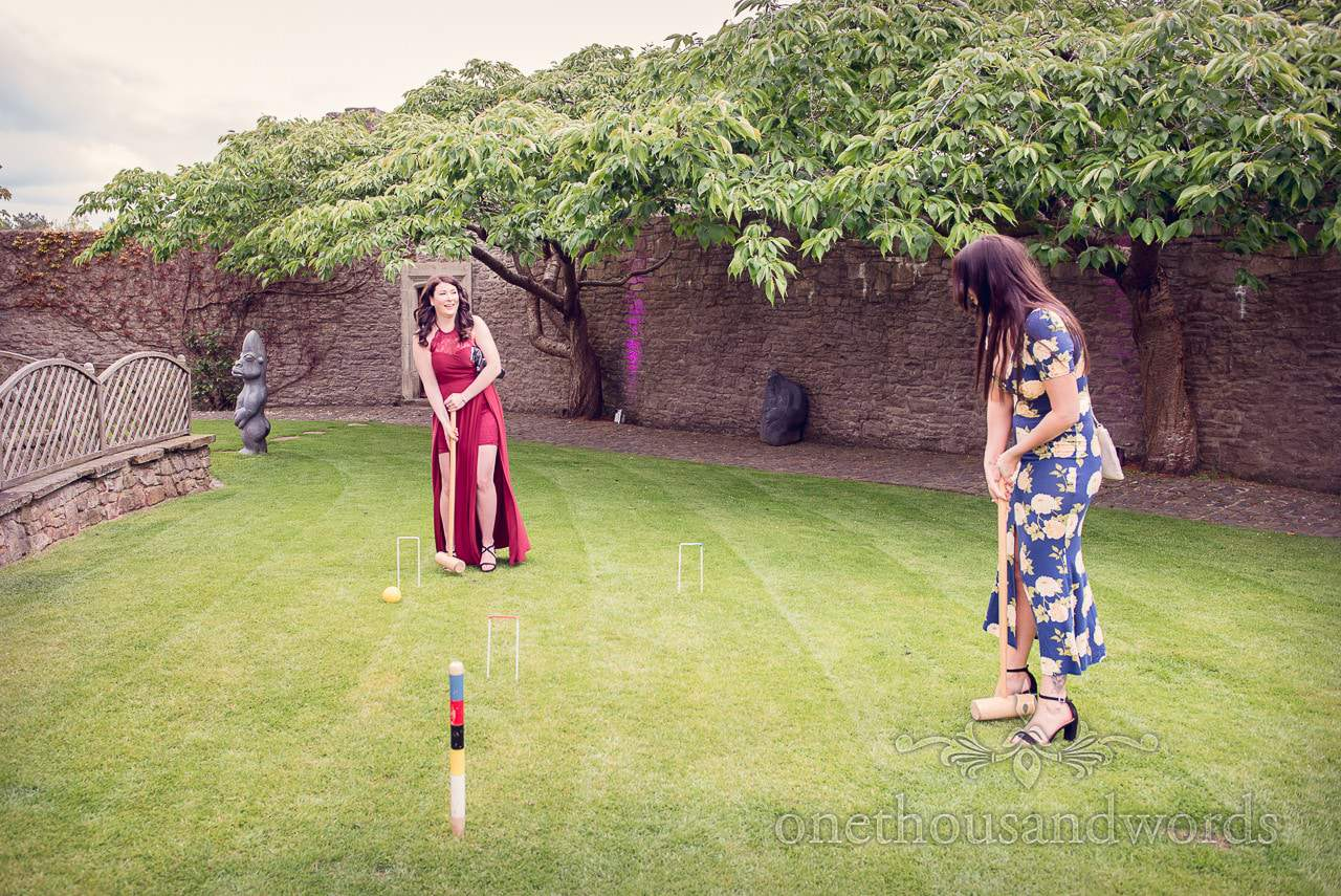 Ladies playing lawn croquet at Walton Castle wedding venue with stone sculptures