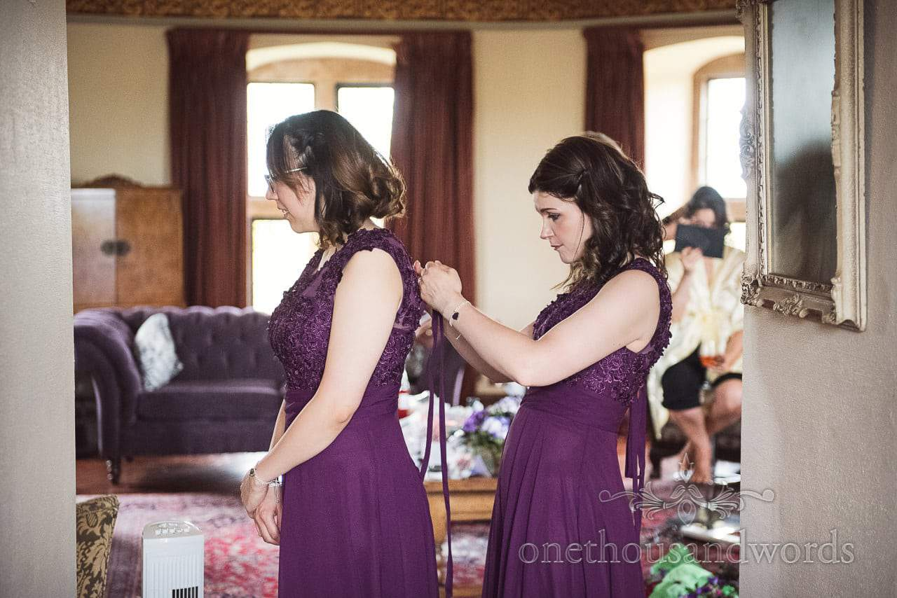 Maid of Honour helps bridesmaid with dress from Chocolate Themed Wedding Photographs