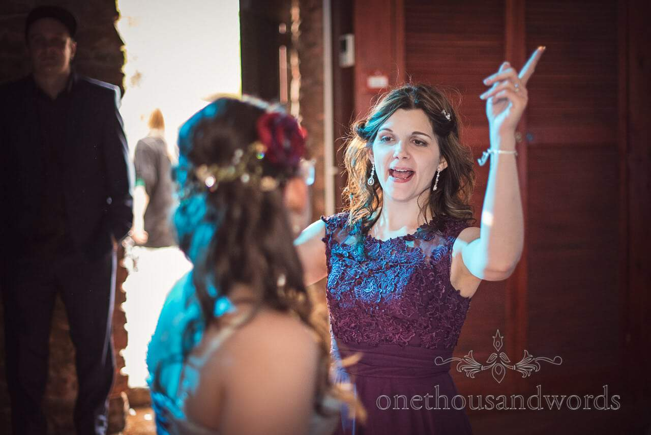 Maid of honour in purple dress dancing at Walton Castle wedding