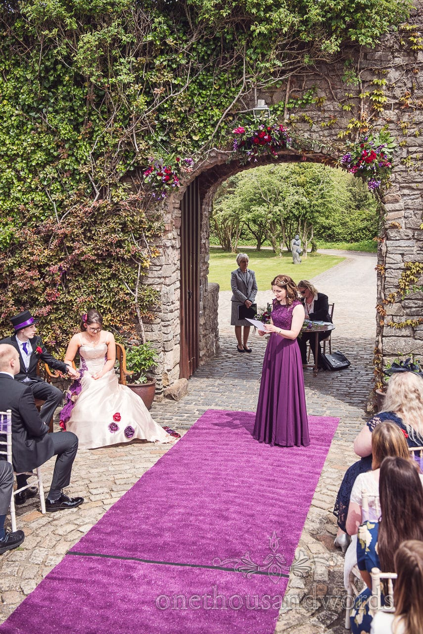 Maid of honour in purple dress gives reading at Walton Castle wedding