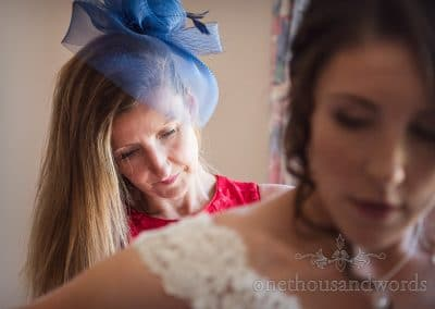 Mother of the bride helps daughter with wedding dress from Swanage Wedding Photos