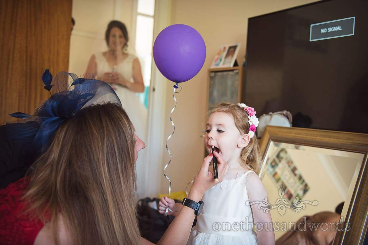 Mother of the bride helps flower girl with lip liner from Swanage Wedding Photos