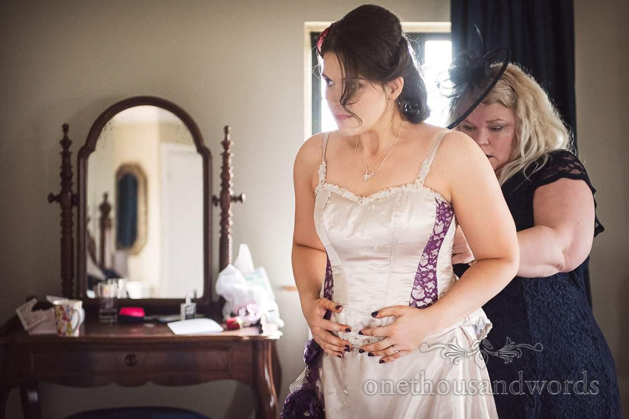 Mother of the bride laces bride into wedding dress at Walton Castle wedding
