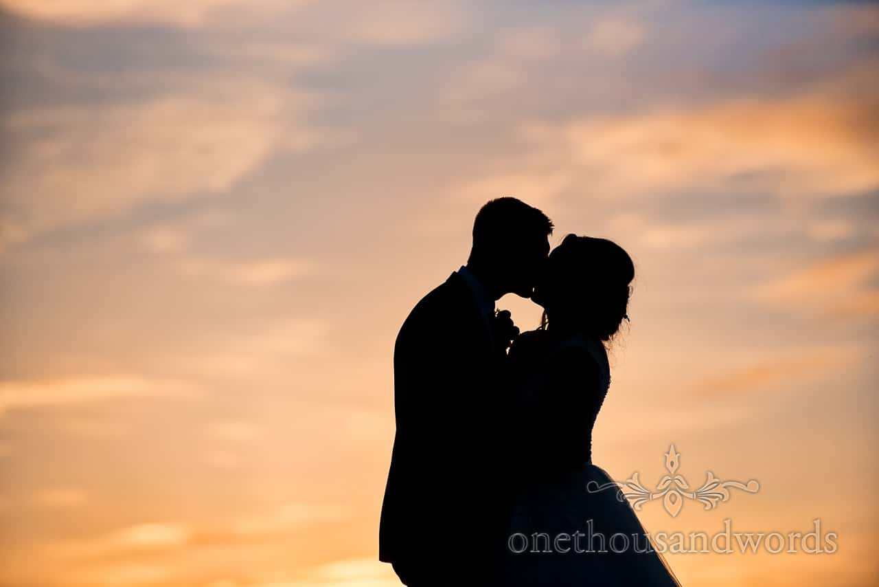 New Mr and Mrs kiss against the sunset sky from Swanage Wedding Photos