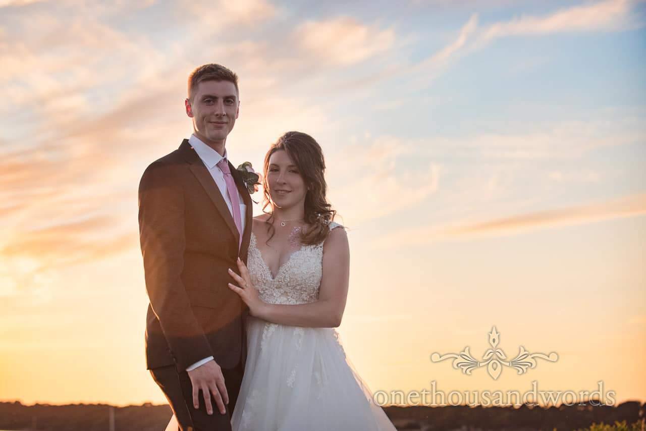 Newlyweds against sunset sky from Swanage wedding photos