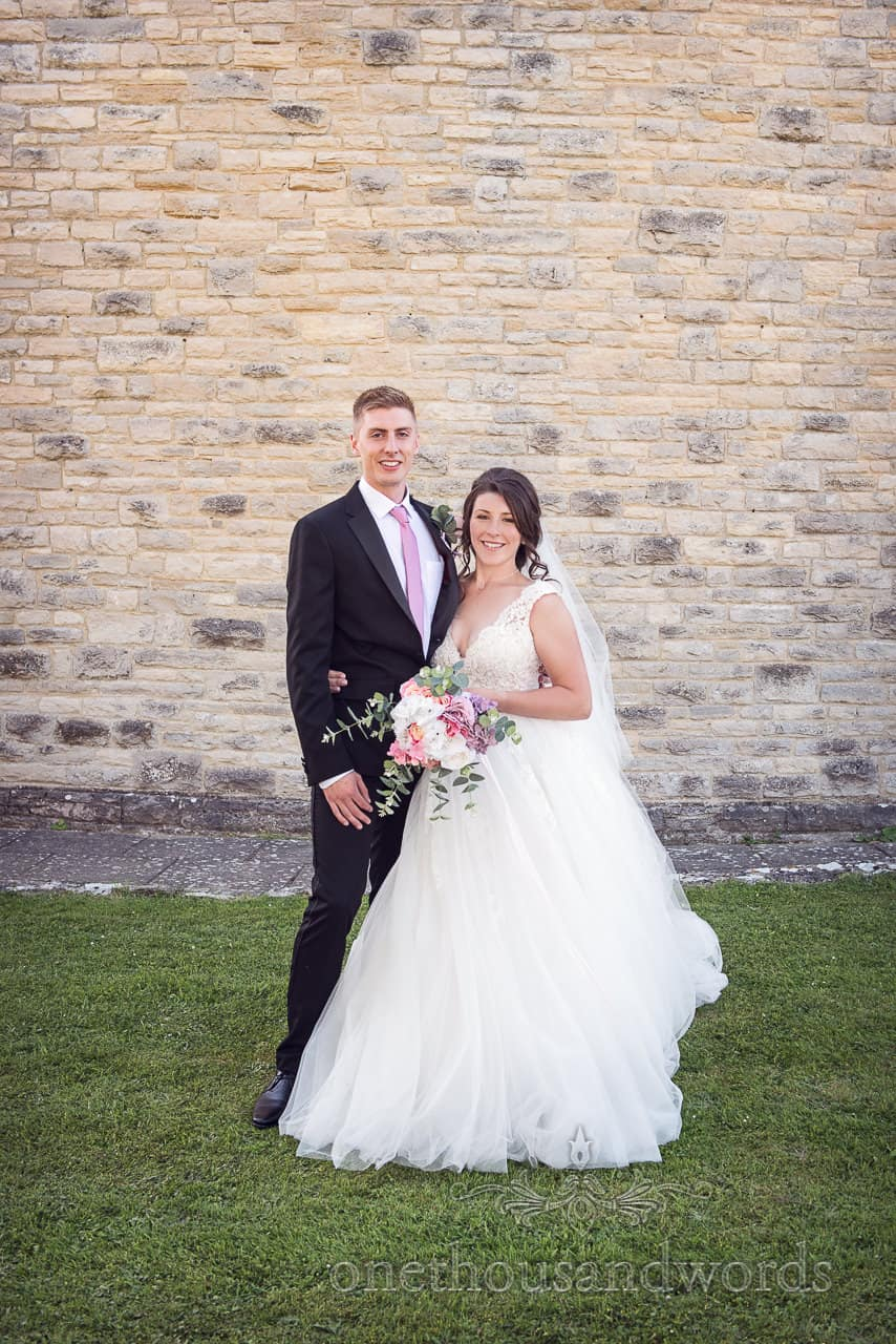 Newlyweds pose for photo outside church from Swanage wedding