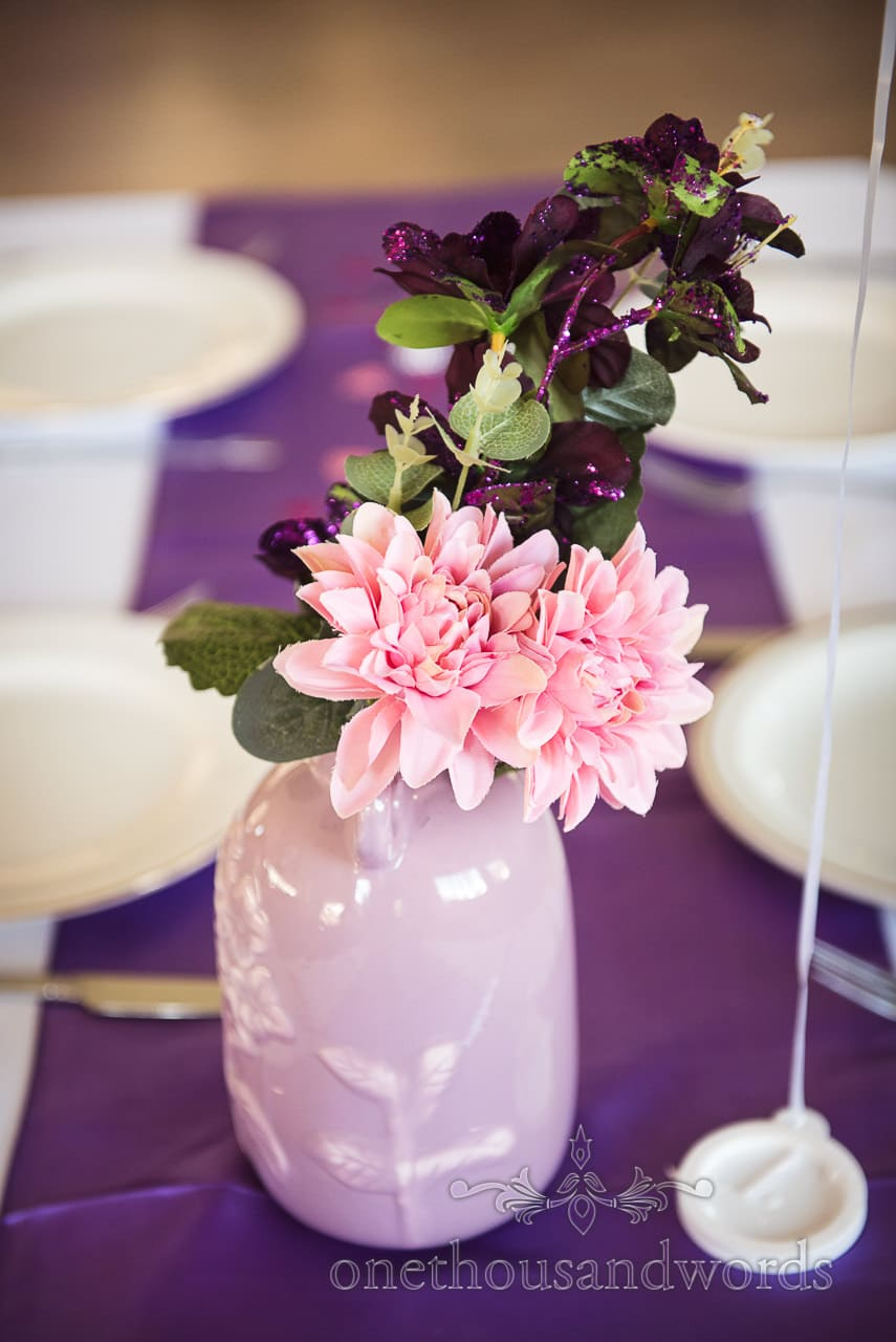 Pink and purple floral table decorations from Swanage wedding photos