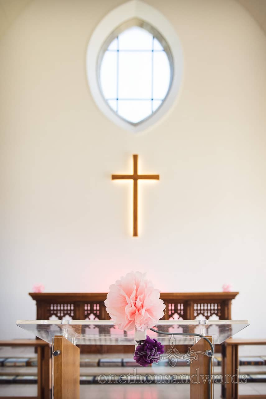Pink and purple paper flower decorations in church from Swanage wedding photos