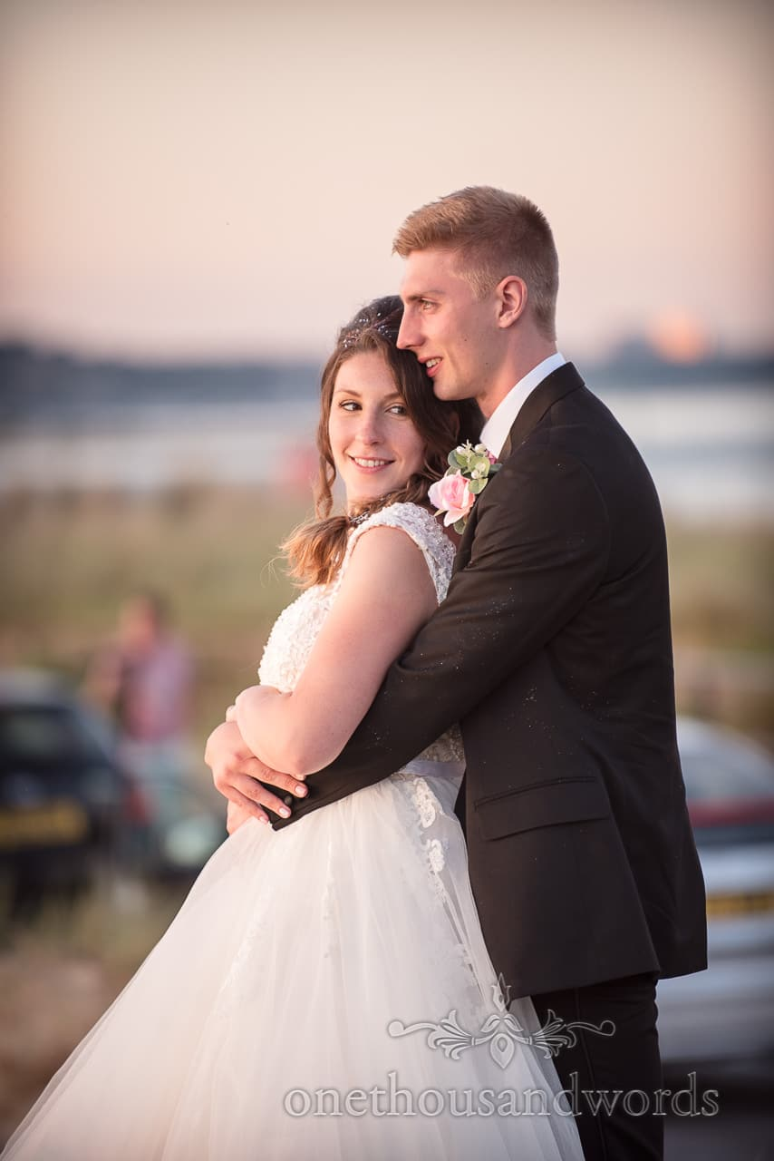 Smiling Bride and groom share embrace at sunset from Swanage Wedding Photos