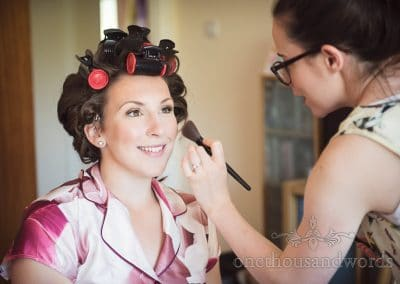 Smiling bride has hair and make up styled at Swanage Wedding Photos