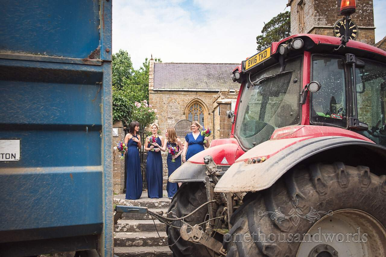 Tractor goes past while bridesmaids are waiting outside church from Countryside Wedding Photos
