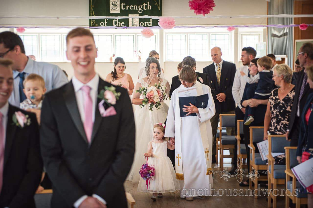 Vicar and flower girl lead wedding party in from Swanage wedding photos