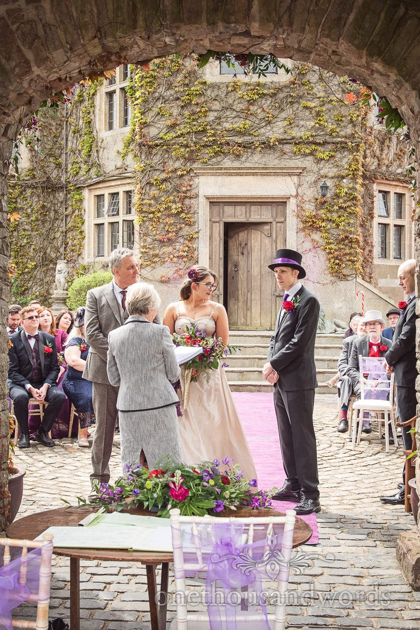 Walton Castle wedding ceremony under stone archway with groom in top hat