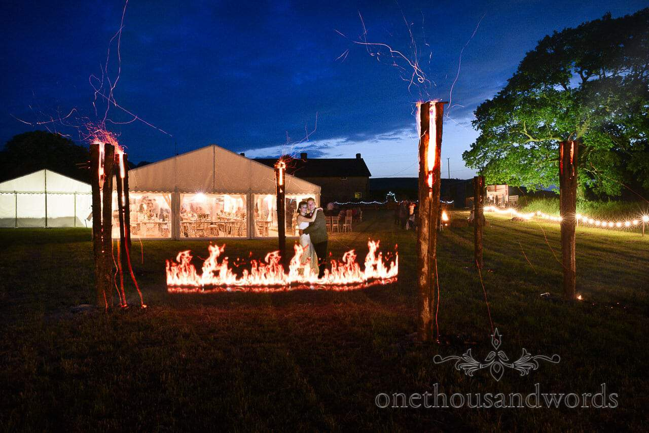 Wedding couple with fire in between giant Swedish torches at countryside wedding