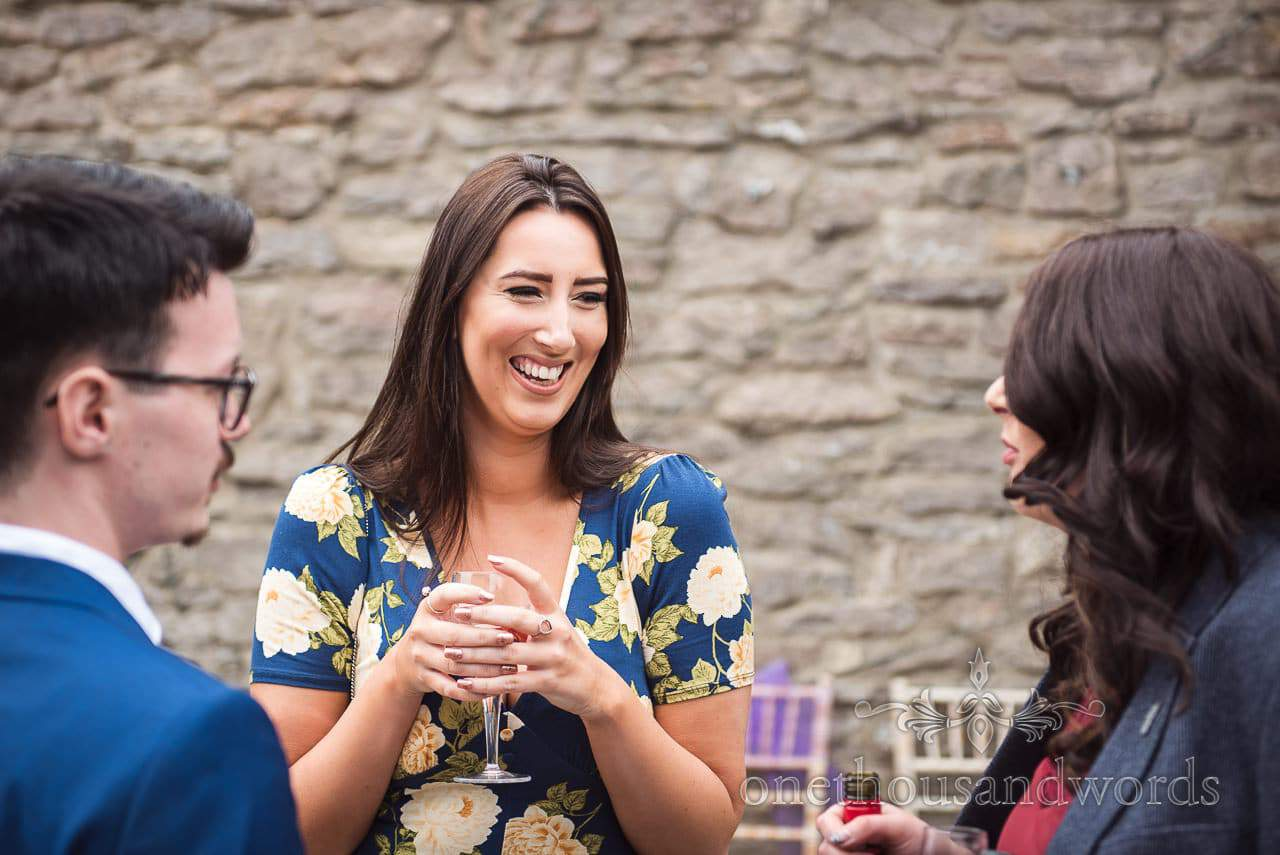 Wedding guest in blue floral dress laughs at Walton Castle wedding drinks reception