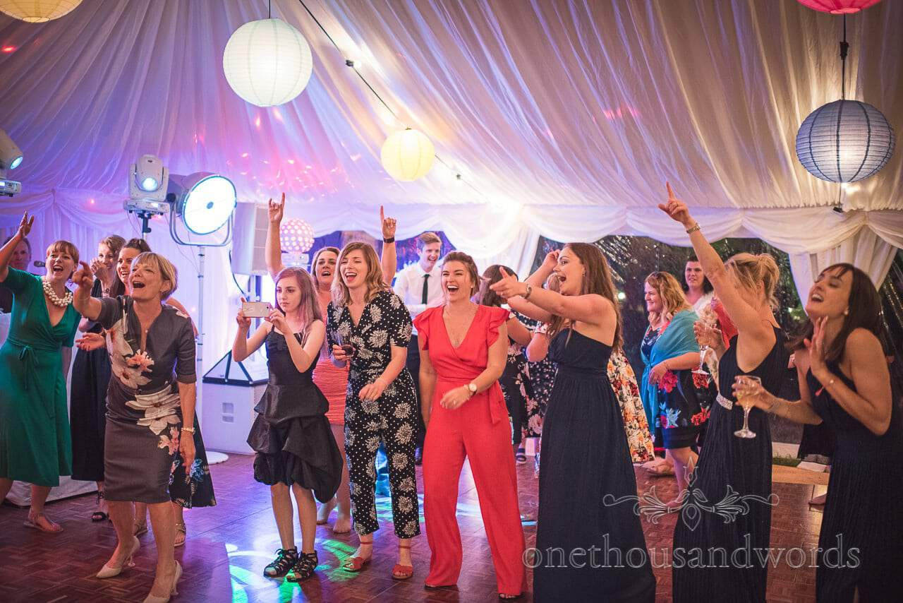 Wedding guests cheer bride and bridesmaids on as they dance in wedding marquee