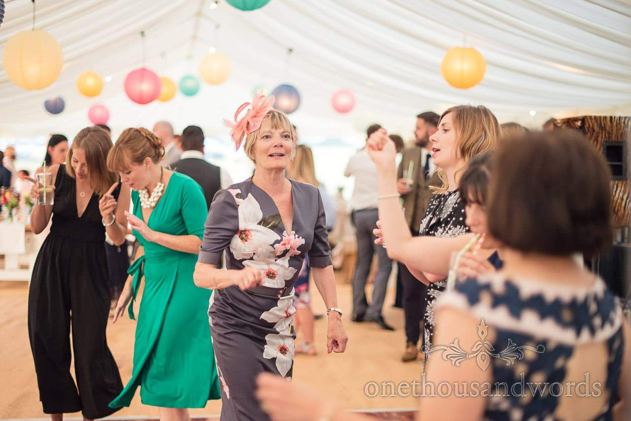 Wedding guests dancing in wedding marquee with multicolour Chinese lanterns