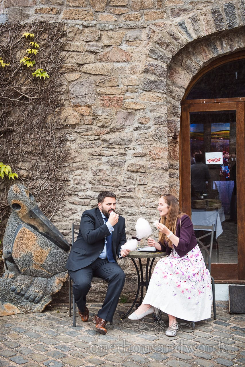 Wedding guests eating candy floss next to stone sculpture at Walton Castle