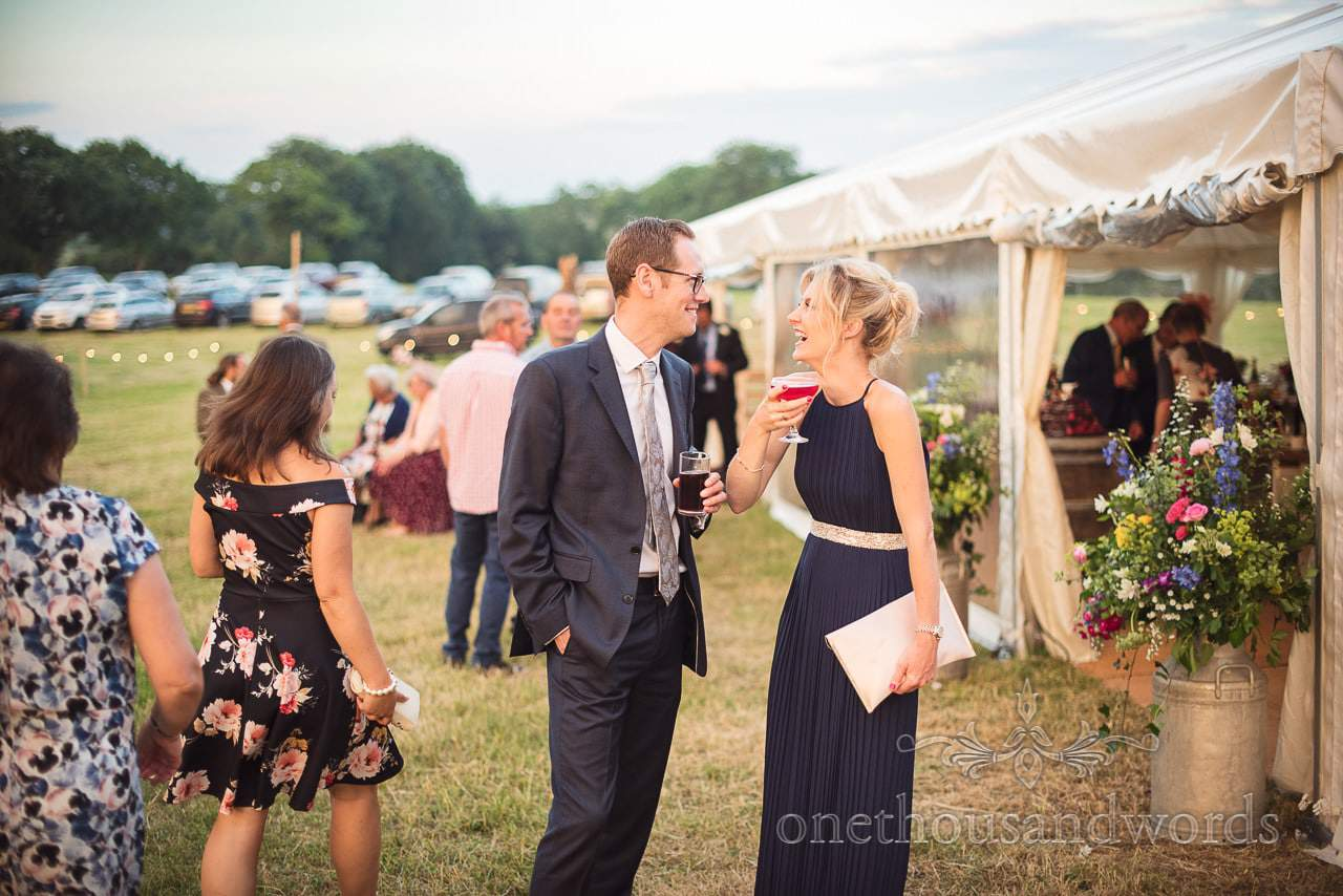 Wedding guests enjoy cocktails outside wedding marquee at countryside wedding