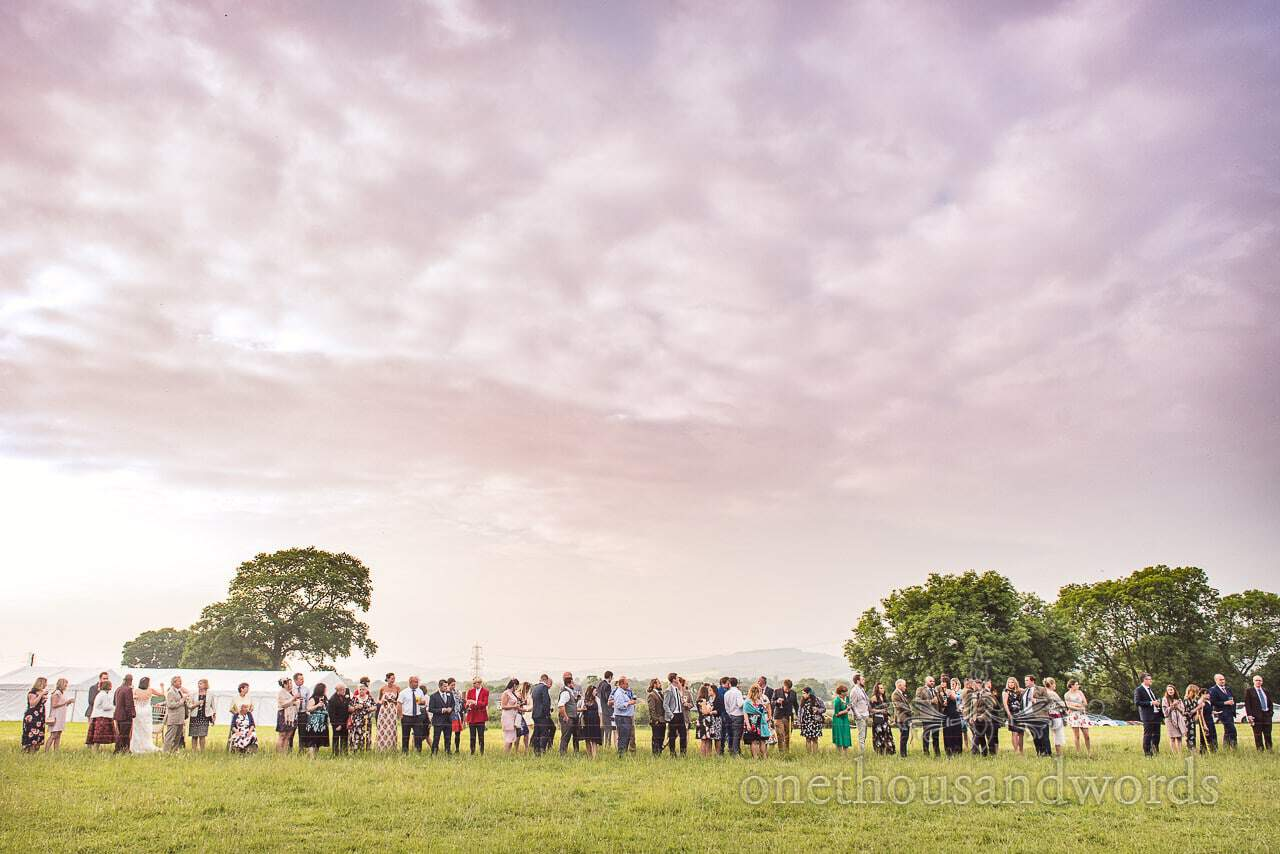 Wedding guests line up under cloudy sky to watch countryside wedding sheep racing