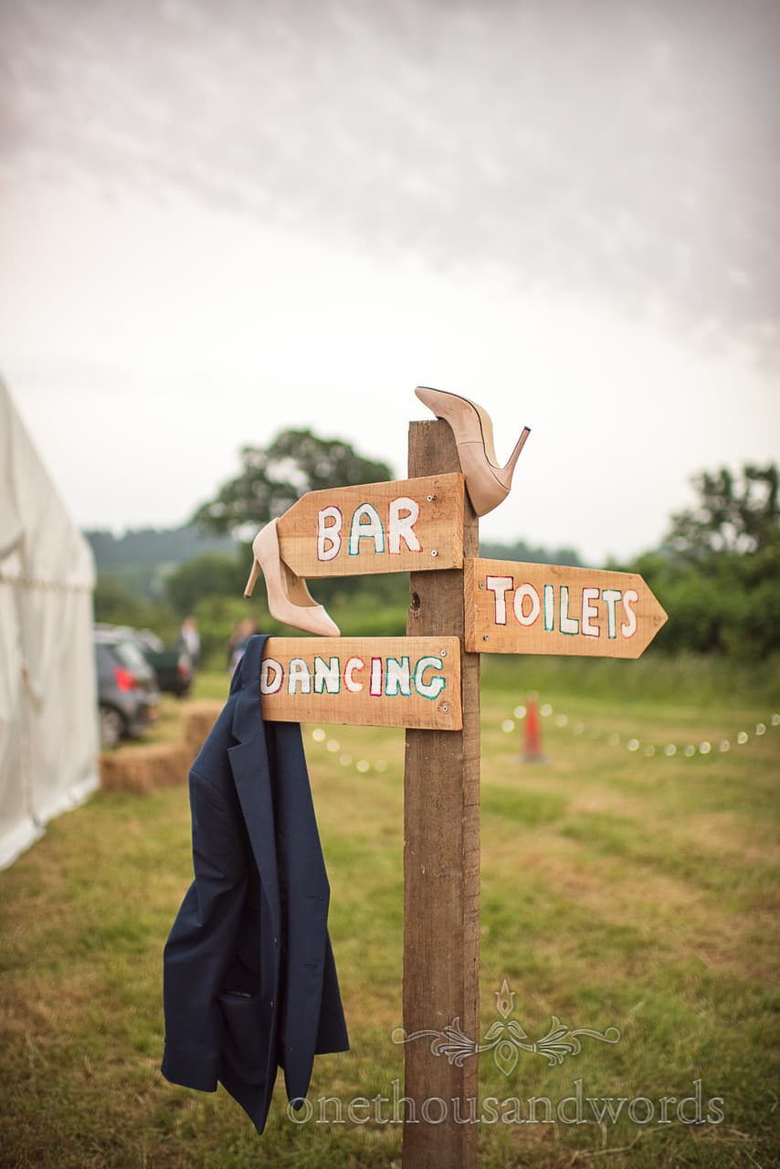 Wooden Bar, Dancing and toilets sign at wedding with heels and jacket hanging