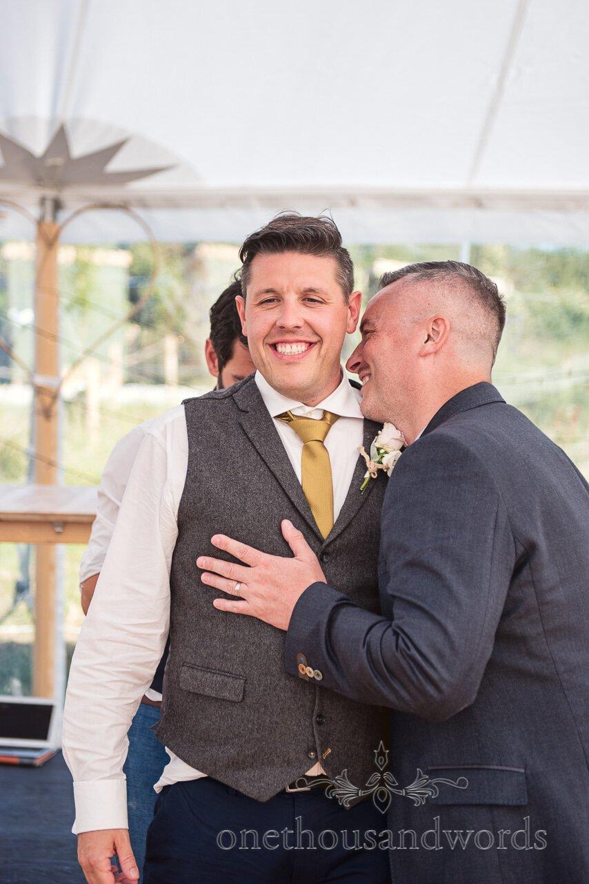 Best man in tweed waist coat is hugged by wedding guest before his wedding speech