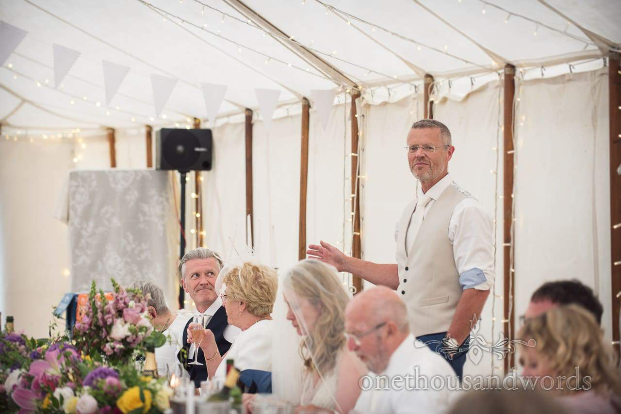 Best man looks at groom during speech at Countryside Manor House Wedding