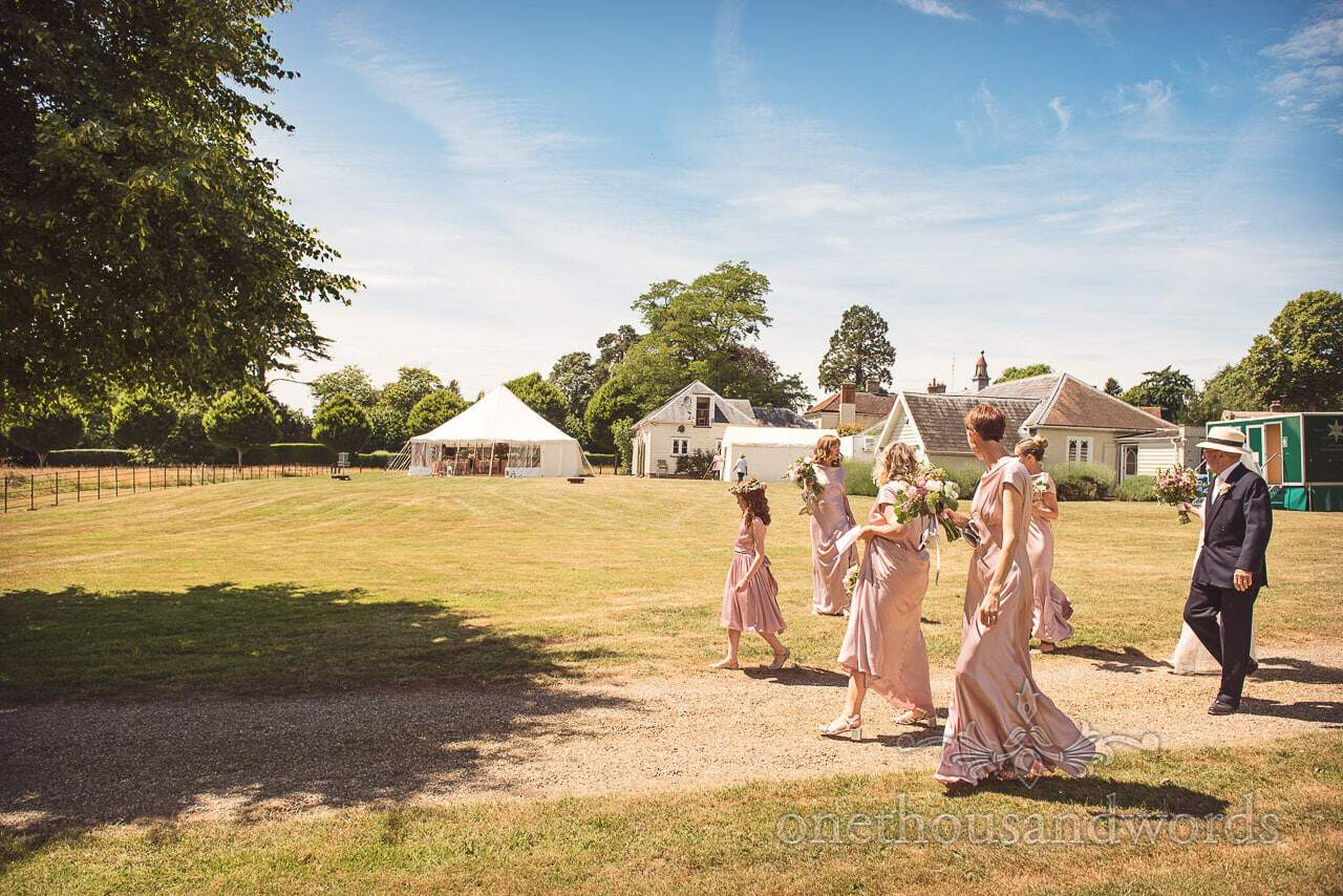 Bride and bridesmaids are escorted to the church from Countryside Manor House Wedding