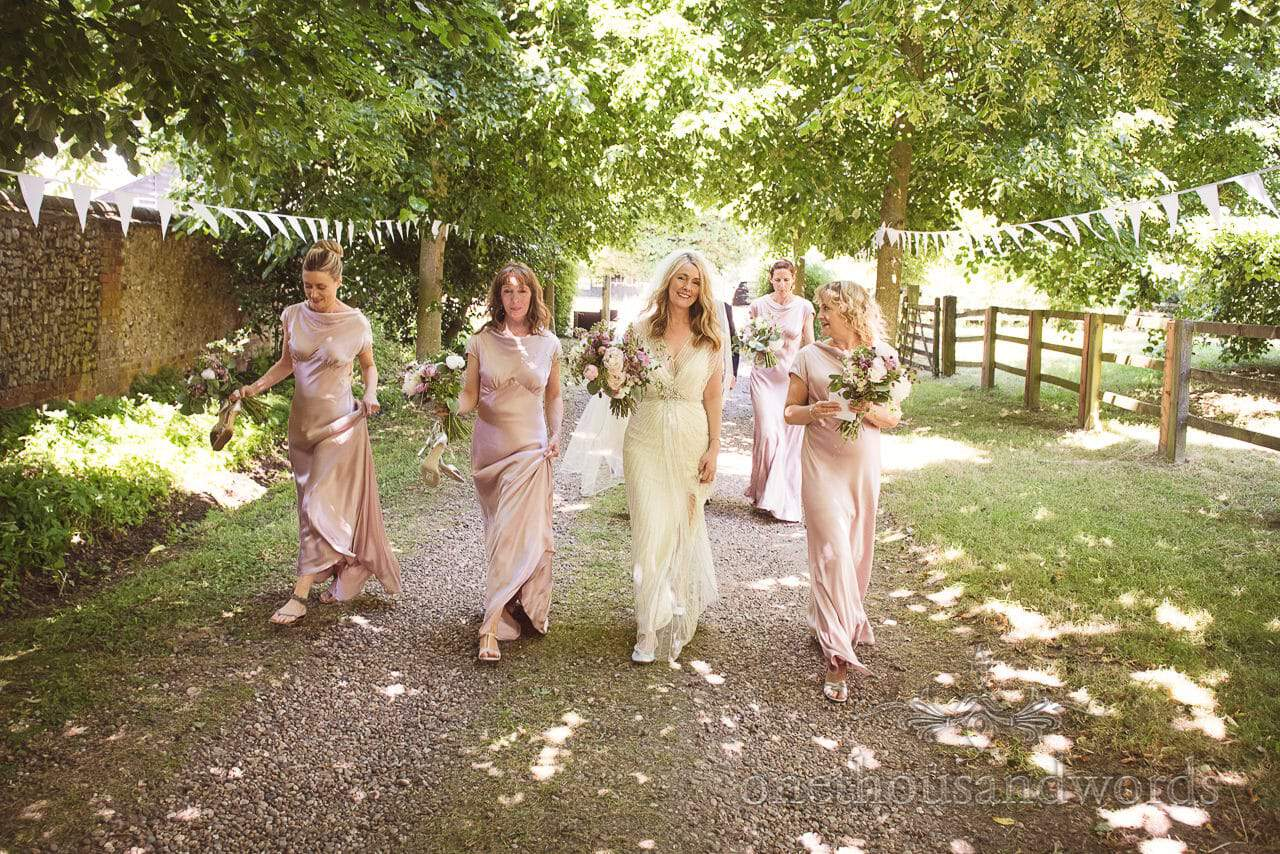Bride and bridesmaids walk down church path from Countryside Manor House Wedding
