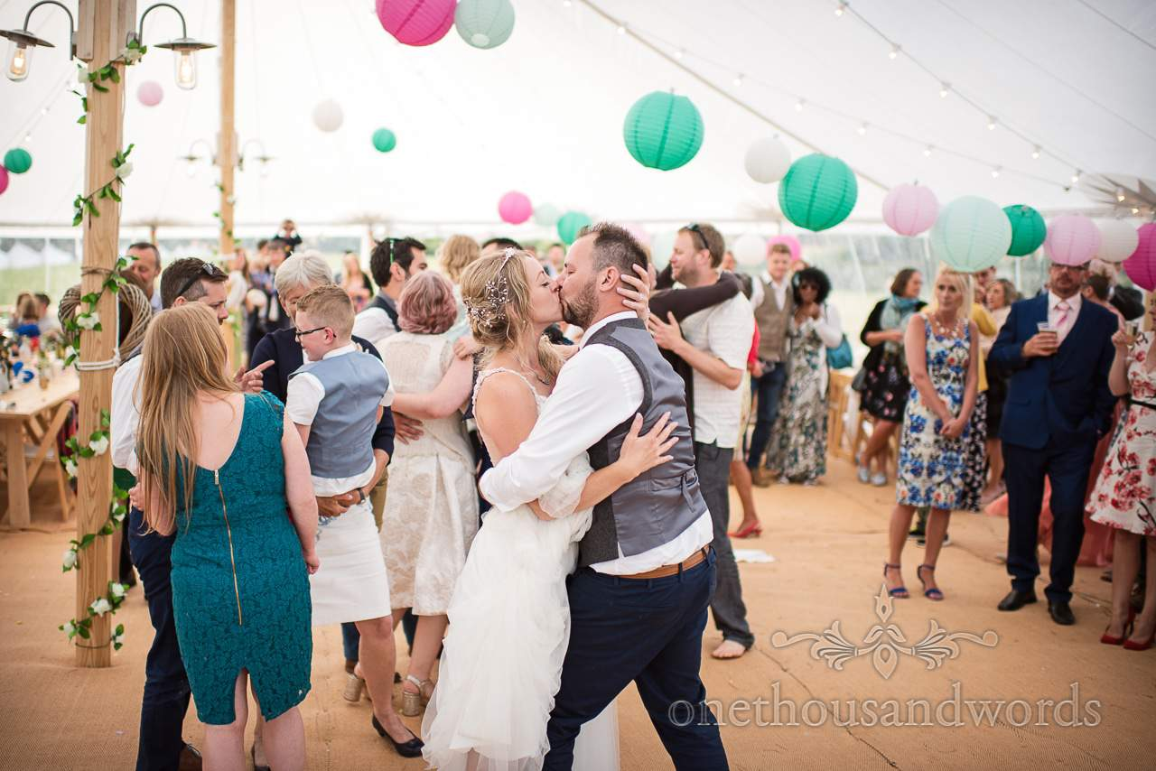 Bride and groom embrace and kiss from Purbeck Valley Farm Wedding Photographs