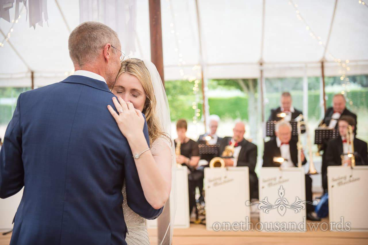 Bride and groom embrace during first dance at countryside wedding