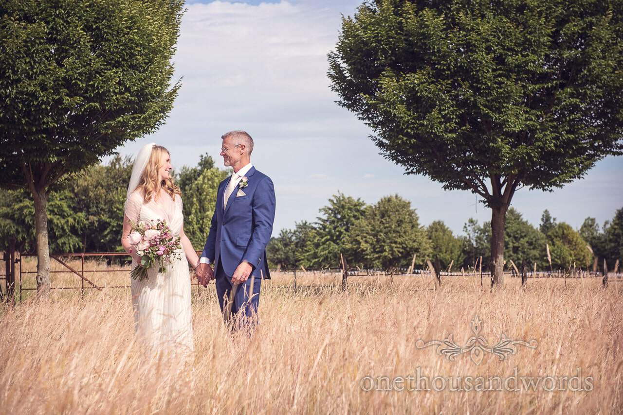 Bride and groom hold hands at Countryside Manor House Wedding