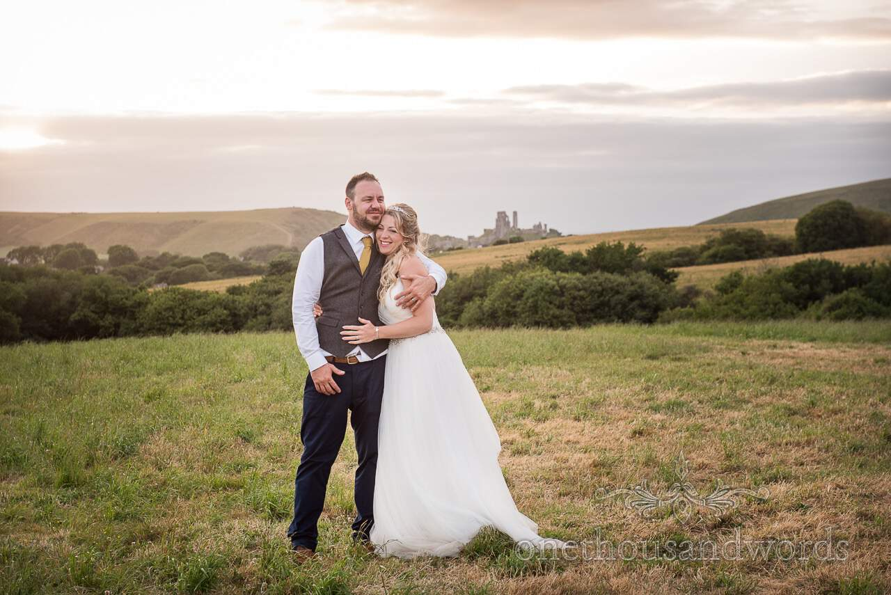 Bride and groom in field near Corfe castle from Purbeck Valley Farm Wedding Photographs