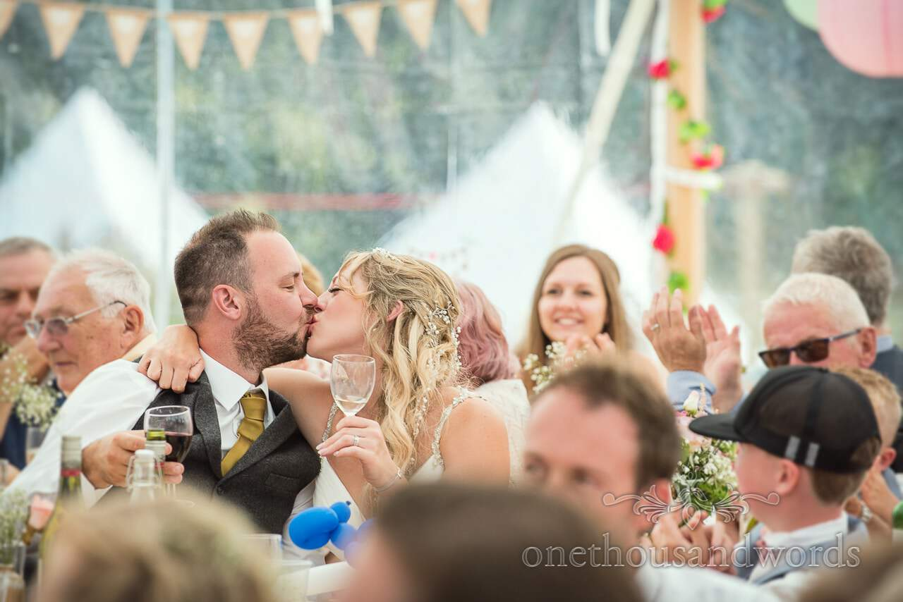 Bride and groom kiss during speeches at Purbeck Valley Farm Wedding Photographs