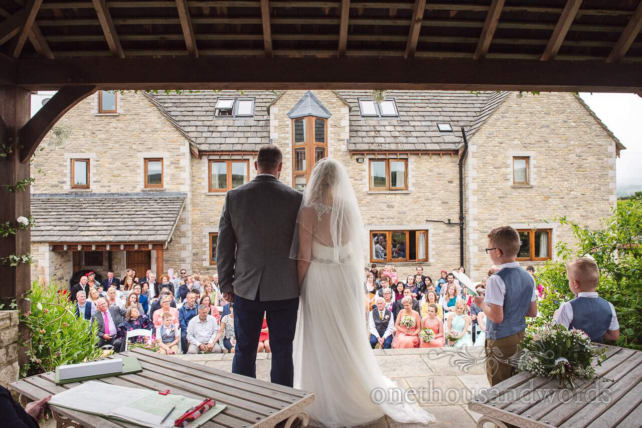 Bride and groom look out towards guests at Purbeck Valley Farm Wedding Photographs
