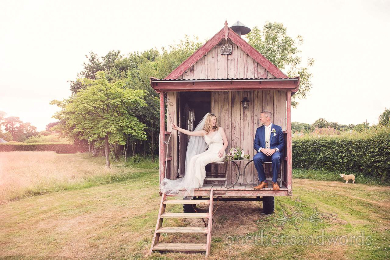 Bride and groom on back porch of wooden caravan at Countryside Manor House Wedding
